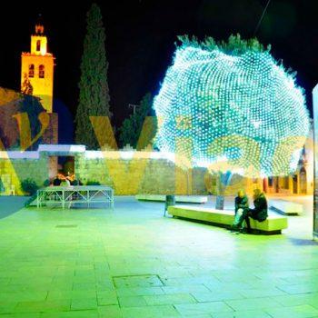 Árbol iluminado con red de luz en una plaza